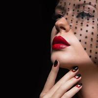 vacker flicka med en slöja, kvällsmakeup, svart och rött foto