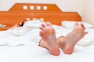 kvinnliga fötter på nära håll sträcker sig när de vaknar foto