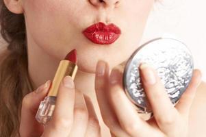 kvinna applicerar röd läppstift medan du ser till handspegeln foto