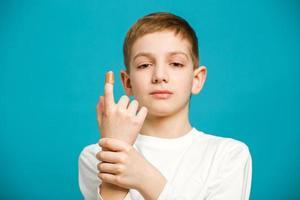 olycklig pojke in med självhäftande gips på tummen