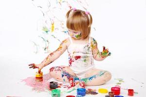 liten flicka bedaubed med ljusa färger foto