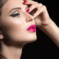 vacker flicka med svarta pilar och rosa läppar och naglar.