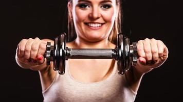 atletisk kvinna som arbetar med tunga hantlar foto