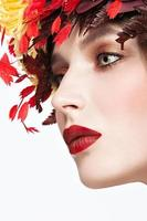 vacker rödhårig tjej med ljus höstkrans av blad foto