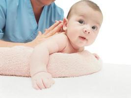 doktor massage liten kaukasiska baby foto