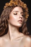 vacker flicka med gyllene smink och höstkrans foto