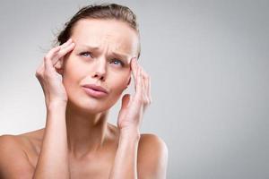 vacker kvinna som lider av akut huvudvärk foto