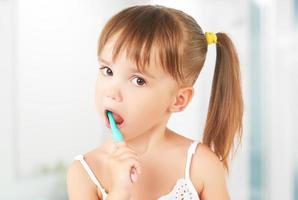glad liten flicka som borstar tänderna foto