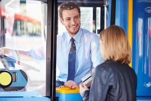 kvinna som går ombord på buss och använder pass foto