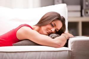 fundersam kvinna på en soffa hemma foto