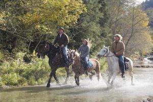 salzburgerland, unga människor som rider hästar över floden foto