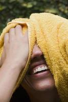 skrattande kvinna som torkar henne, huvudskott foto