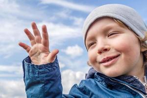skrattande pojke med molnig bakgrund foto