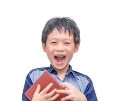 pojke skrattar mellan att läsa en bok foto