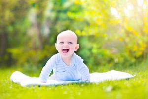 söt skrattande baby i trädgården foto