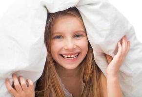 skrattande liten flicka under en filt foto