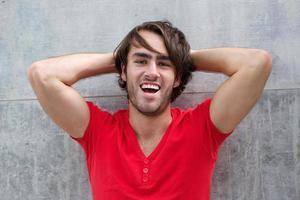 ung man skrattar med handen i håret foto