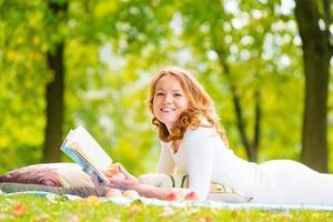 skrattande tjej med bra bok på gräset foto