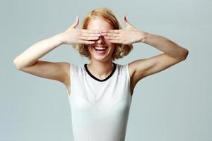 skrattande kvinna stänger ögonen med händerna o foto