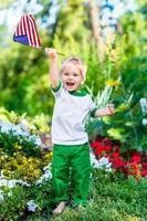 barfota liten pojke som skrattar och viftar med amerikanska flaggan foto
