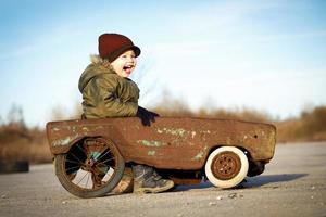 glad pojke och hans leksaksbil foto