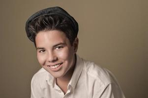 skrattande pojke med ett mössa på en brun bakgrund foto