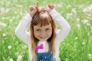 liten flicka som skrattar och leker med sina händer som representerar get foto