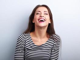glad naturlig skrattande ung casual kvinna med vidöppen mun foto