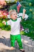 rolig skrattande liten pojke med blont hår som håller amerikanska flaggan foto