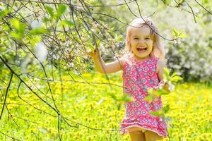 glad liten flicka i soligt vår park