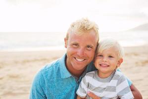 far och son på stranden foto
