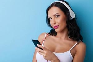 vacker ung kvinna med hörlurar är avkopplande foto