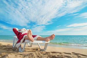 sola jultomten avkopplande på tropisk sandstrand foto