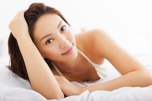ung vacker asiatisk kvinna som kopplar av på sängen foto