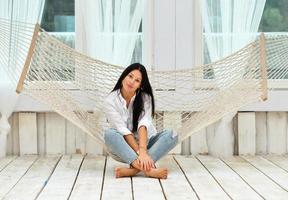 vacker leende ung kvinna som kopplar av i hängmatta hemma foto