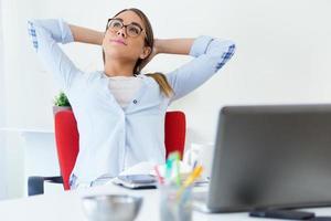 ganska ung kvinna kopplar av ett ögonblick på sitt kontor. foto