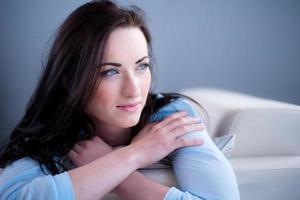 porträtt glad ung brunett liggande på soffan avslappnad hemma foto