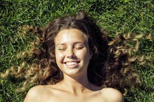 ung söt sommarflicka på gräs utanför avkopplande leende foto