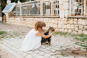 liten flicka som leker med katt utomhus foto