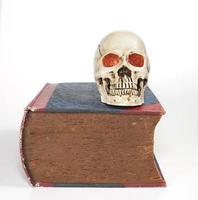 skalle och stor gammal textbok foto