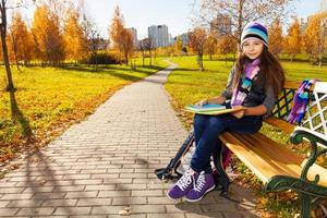 skolflicka med läroböcker i parken