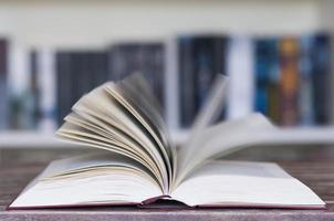 öppnad bok framför bokhylla foto