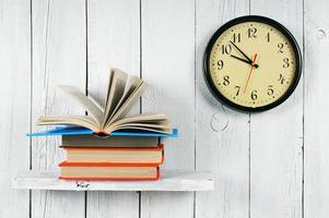 den öppna boken på en trähylla och klockor. foto
