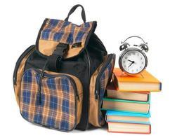 skolryggsäck, böcker och väckarklocka. foto