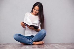 flicka sitter på golvet och läser bok foto