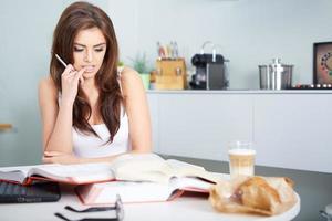 ung studentkvinna med massor av böcker som studerar foto
