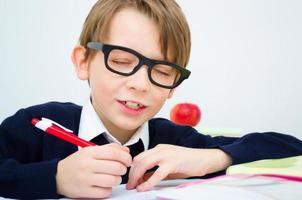 skolpojke som skriver läxor foto