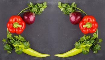 färska grönsaker på mörk svart tavla foto