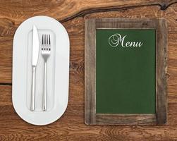 svarta tavlan med vit platta, kniv och gaffel foto