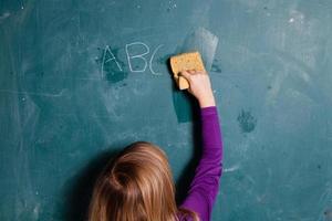 ung flicka torkar svarta tavlan med våt svamp